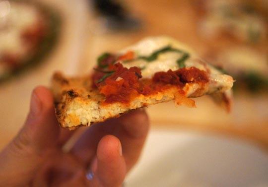 "<img src=""slice_of_cauliflower_pizza.png"" alt=""holding a slice of cauliflower pizza""/>"